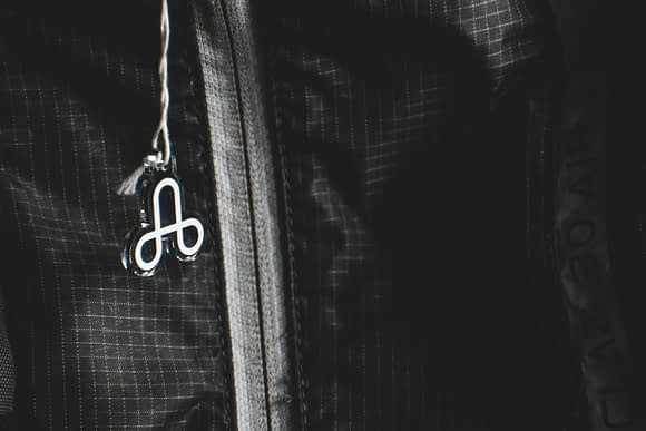A backpack displaying the acrylic charm featuring the logo